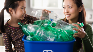 Mum and daughter recycling green plastic bottles